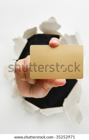Hand breakthrough wall holding empty golden card - one of the breakthrough series - stock photo