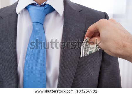 Hand bribing businessman by putting money in his pocket - stock photo