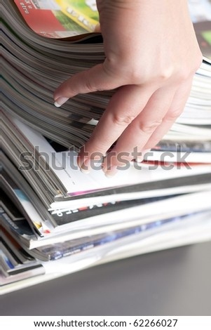 hand browsing through stack of magazines