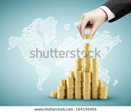 hand building coins chart and drawing world map - stock photo
