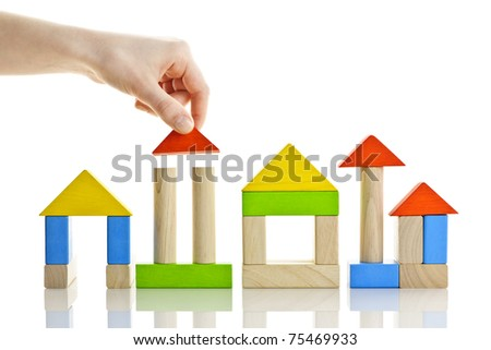Hand building houses of wooden block toys isolated on white background - stock photo