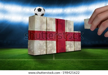 Hand building wall of england flag in grunge effect - stock photo