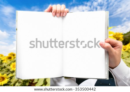 Hand businessman holding book outdoor green fields.
