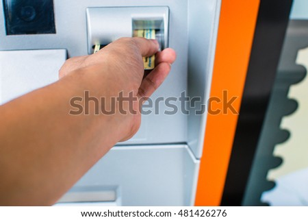 hand businessman inserting ATM credit card into  machine to withdraw money