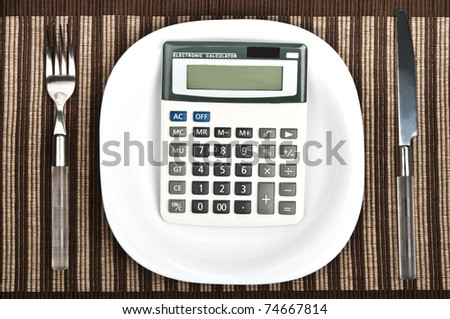 Hand calculator on plate with fork and knife - stock photo