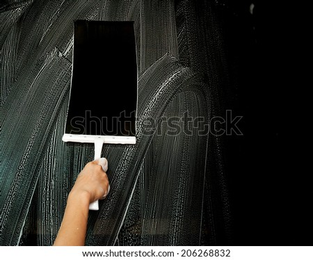 Hand carefully cleaning window. - stock photo