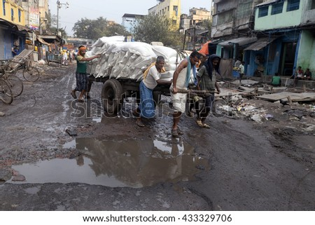Hand cart puller try to save their goods from hole filled with water on February 27, 2016 in Calcutta, India.