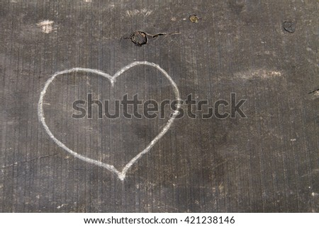 Hand-carved heart shape on a wooden board. - stock photo