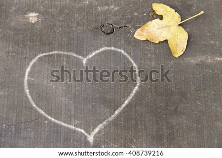 Hand-carved heart shape on a wooden board and yellow, wilted leaf beside. - stock photo