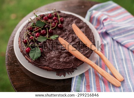 hand carved wooden knife and a chocolate cherry pie - stock photo