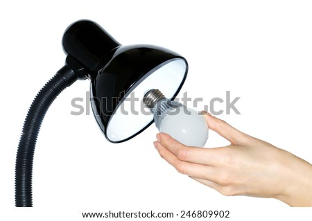 Hand changing a regular light bulb for LED at home  - stock photo