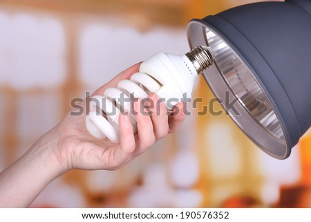 Hand changing light bulb for lamp at home - stock photo