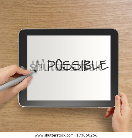 hand changing the word impossible to possible with stylus eraser on tablet computer as concept  - stock photo
