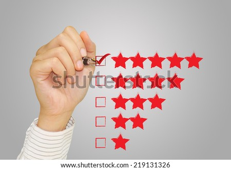 Hand check mark with red marker on five star rating. - stock photo