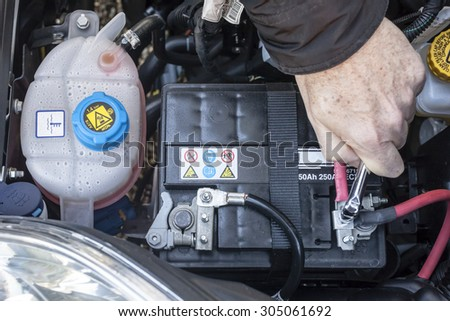 Hand checking the clamp nut of a car battery with a wrench