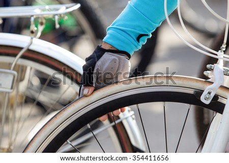 Hand checks the amount of air in a bicycle wheel - stock photo