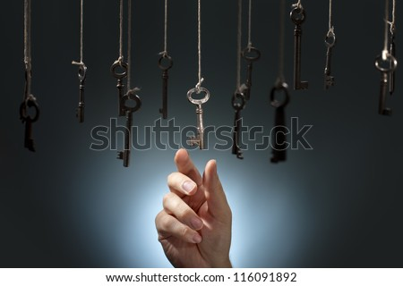 Hand choosing a hanging key amongst other ones. - stock photo
