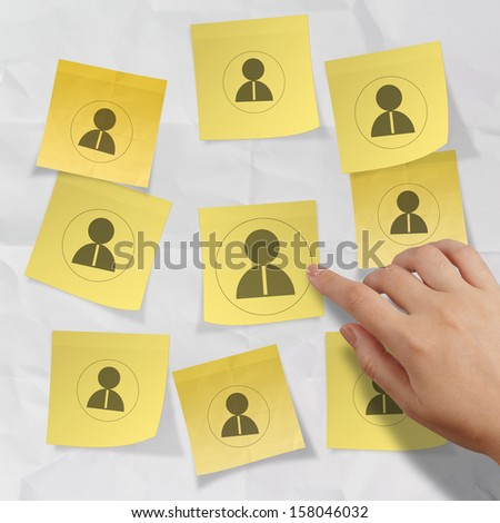 hand choosing people icon on sticky note with crumpled paper as human resources concept - stock photo