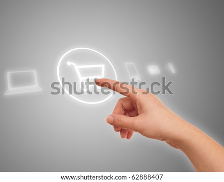 hand choosing shopping cart symbol from media icons on grey - stock photo