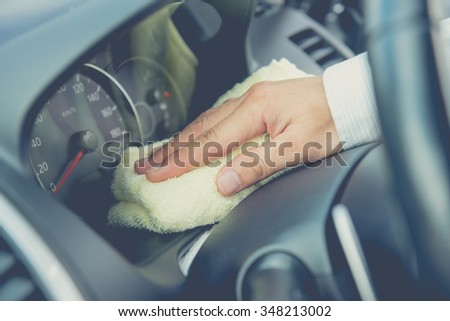 Hand cleaning car dashboard with microfiber cloth, wipe interior ,vintage tone ,finger focused