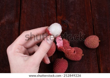 Hand, cleaning litchi from the shell. Tasty and delicious lychee fruit. Chinese plum, Litchi chinensis - stock photo