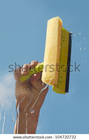 Hand cleaning window against blue sky. - stock photo
