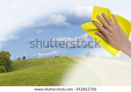 hand cleaning window making it easier to see beautiful landscape on a sunny day - stock photo