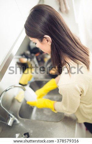 Hand cleaning.Young housewife woman washing dishes in kitchen.Cleaning and washing dishes and pans with yellow rubber gloves.Cleaning kitchen.Tiring and boring manual housework.Housekeeping.Chores - stock photo