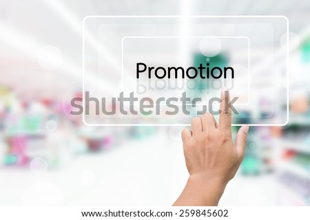 Hand Clicking On Promotion Screen With Supermarket Shelves Blurred Background - stock photo