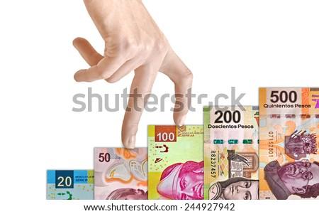 Hand climbing a Mexican peso bill mountain - stock photo