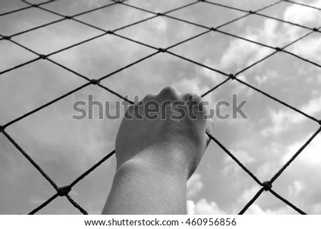 Hand climbing link fence , black and white. Concept of imprisonment. break free - stock photo