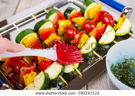 Hand coating fresh prepared vegetable skewers with tomato, pepper and zucchini with herb dip - stock photo