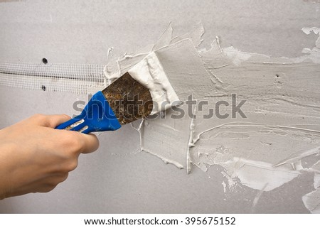 hand coating wall of plaster with spatula  - stock photo