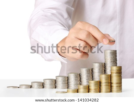 hand coins in finger and row stacks them isolated on white background - stock photo
