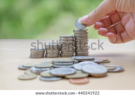 hand collect  stack of coins on nature bokeh background : concept of saving money - stock photo