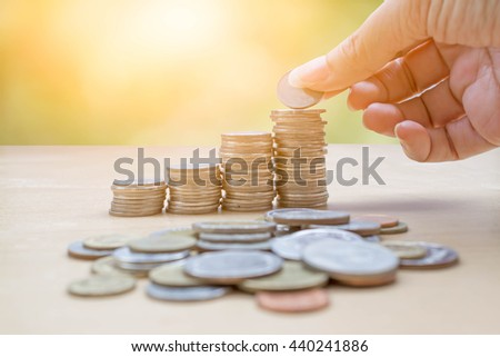 hand collect  stack of coins on nature bokeh background with sunlight : concept of saving money - stock photo
