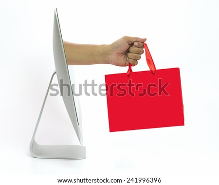 Hand come out from computer screen holding shopping bag. On line business concept