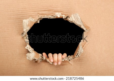 Hand coming out from hole in a corrugated cardboard with black background  - stock photo