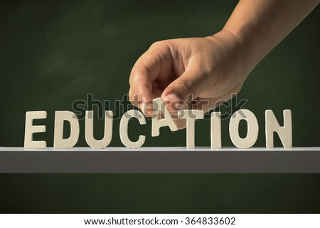 hand completes the education word - stock photo