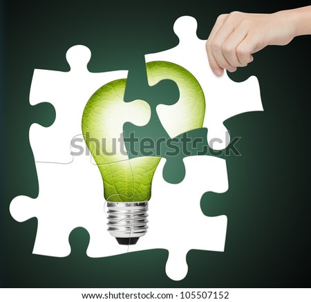 hand completing jigsaw puzzle of  green energy light bulb, sign of environment saving - stock photo