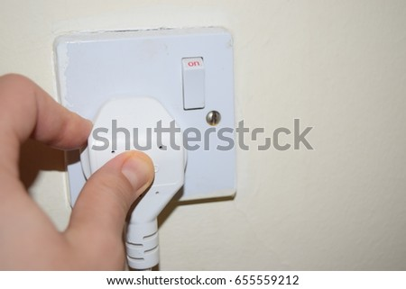 Hand connecting electrical plug. Man holding electric power plug. Connecting power plug. Electricity concept. Hand Putting Plug Into Electricity Socket