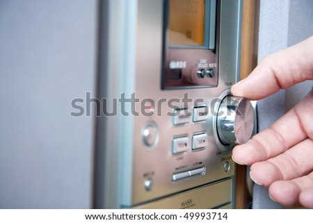 Hand controlling  volume of a stereo recorder - stock photo
