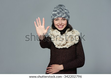 Hand counting - five fingers. Portrait of woman wearing woolen hat and muffler showing five fingers, giving high five gesture - success and winning concept. - stock photo