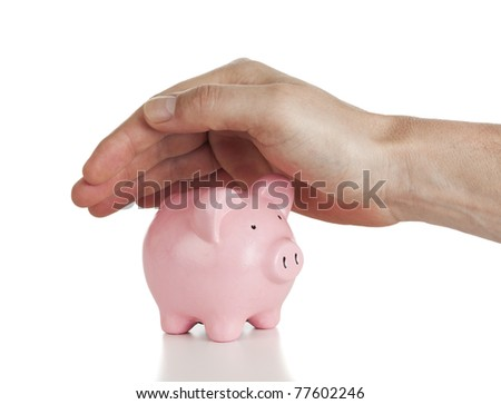 hand covering small piggy bank isolated on white