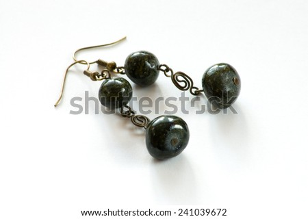 Hand crafted earrings made with metal and black stones isolated on the white background