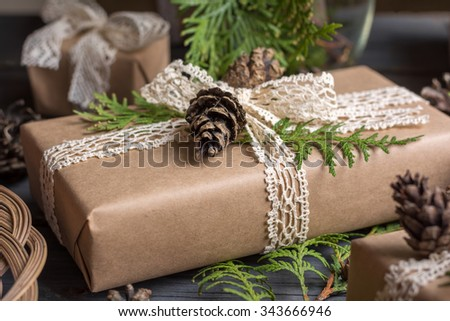 Hand crafted gift decorated branches of thuja and cones. Closeup shot - stock photo