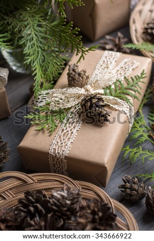 Hand crafted gift on wooden table with branches of thuja and cones - stock photo