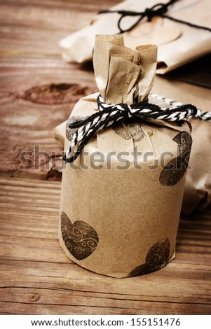 Hand crafted gifts on rustic wooden table - stock photo