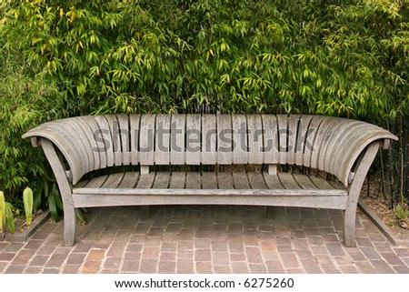 Hand crafted Japanese wooden oak curved bench, standing on a tiled terrace with bamboo plants to the rear.