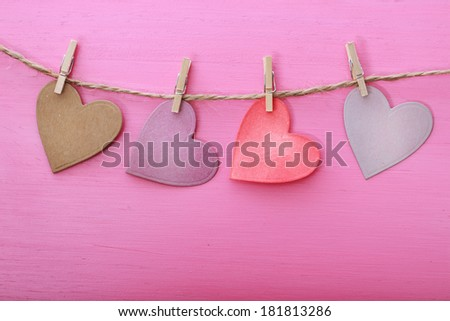 Hand-crafted paper hearts hanging with clothespins over pink wooden board - stock photo